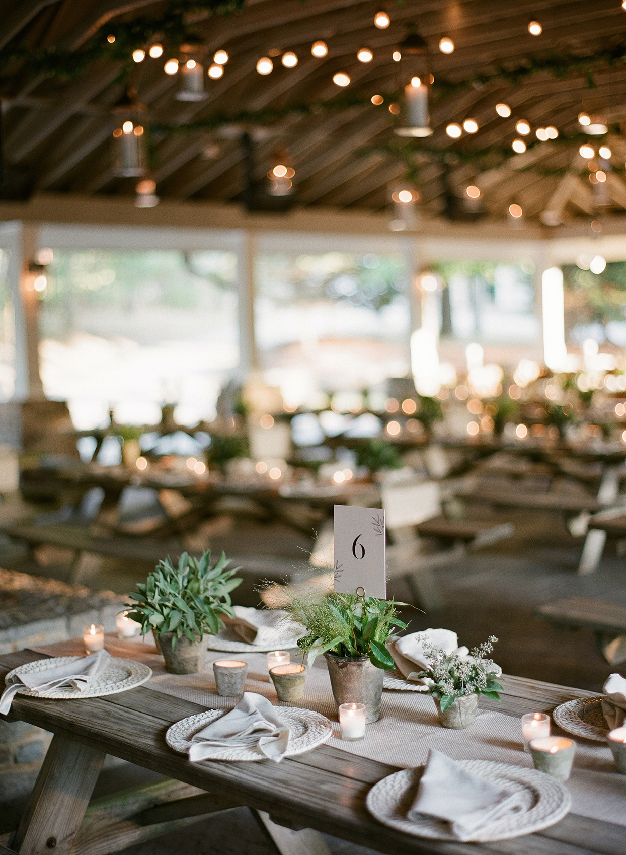 rehearsal dinner wooden long picnic tables set in neutral colors