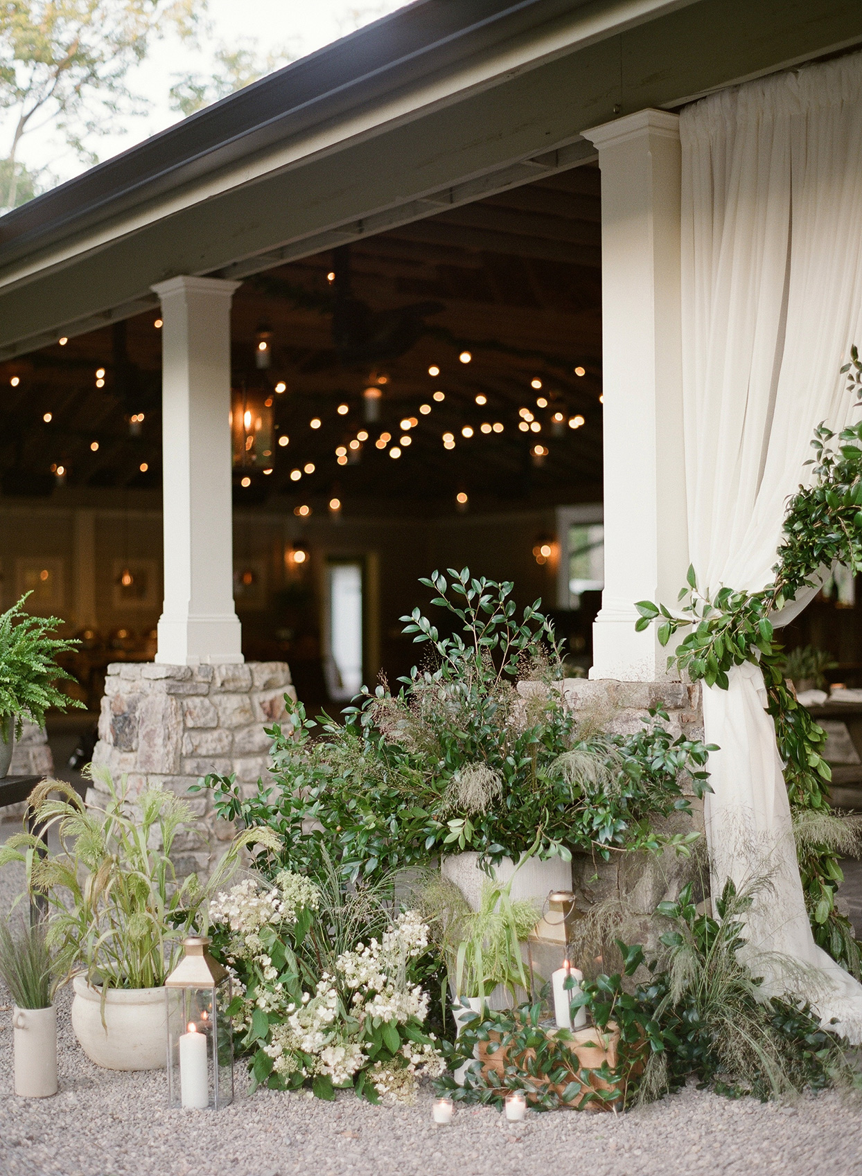 draped tent with floral and greenery display by stone shelter bases