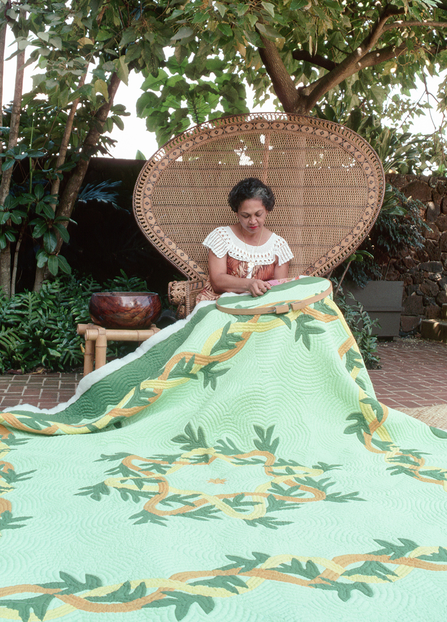 woman hand stitching Hawaiian quilts