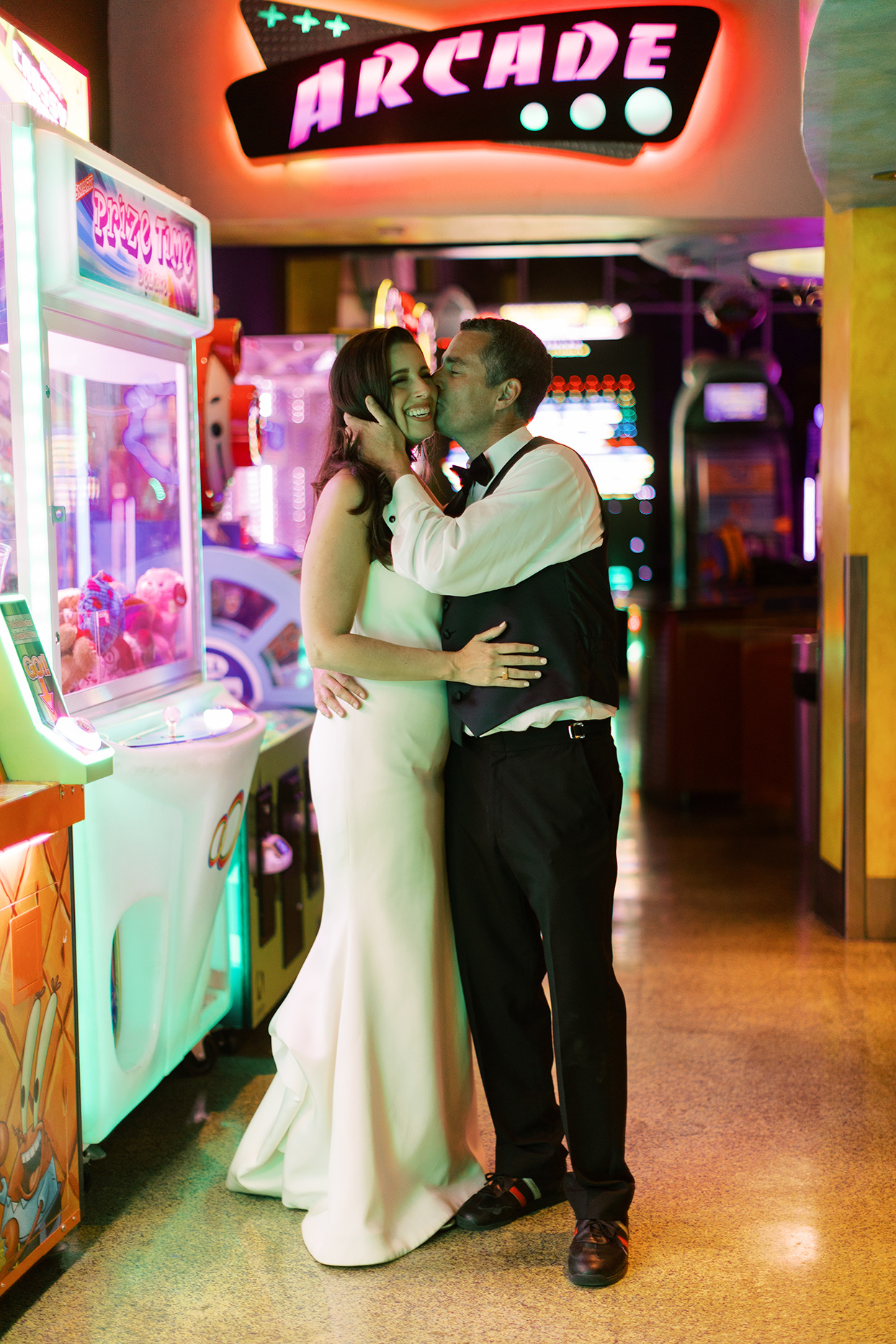 bride and groom at arcade after party under neon light