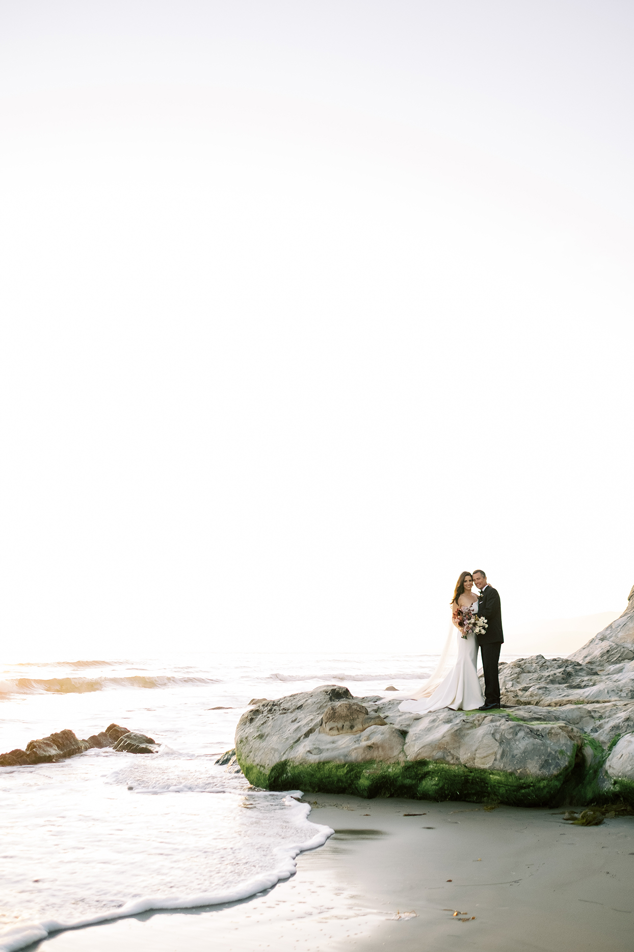 wedding couple posing for portraits on rock at the beach