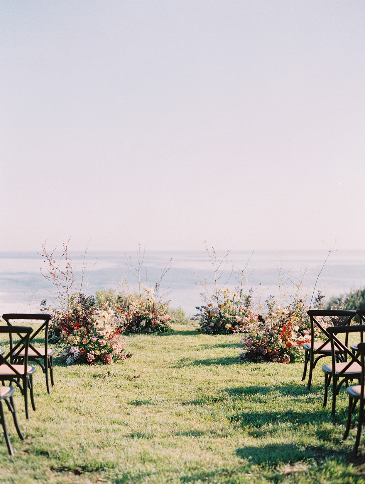 wedding ceremony location by the ocean with pods of floral decor