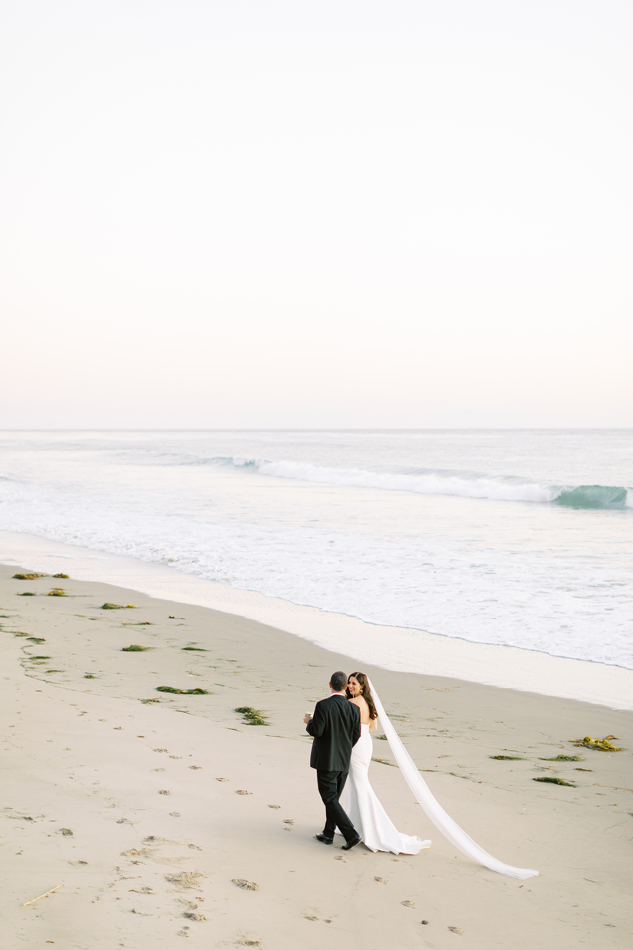 wedding couple walking and talking together on the beach