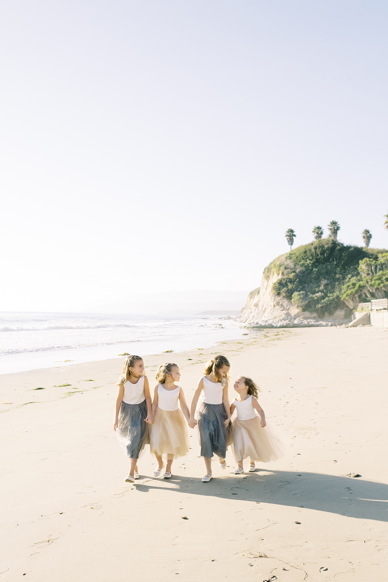 flower girls walking hand in hand on beach