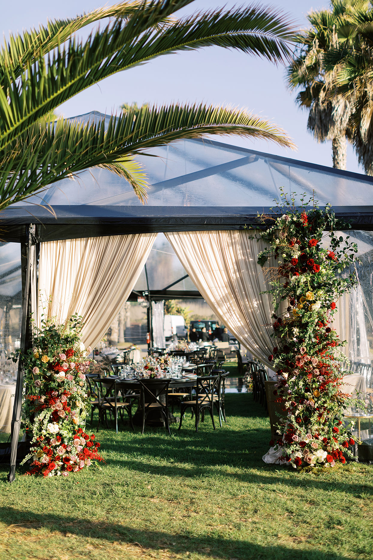 wedding reception tent on lawn with elegant florals and black tables