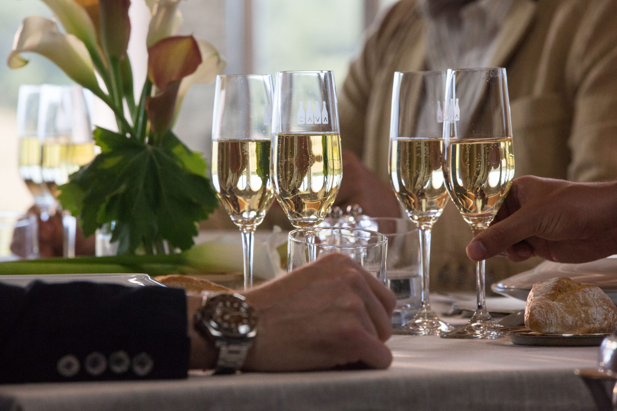hands reaching for glasses of cava on table