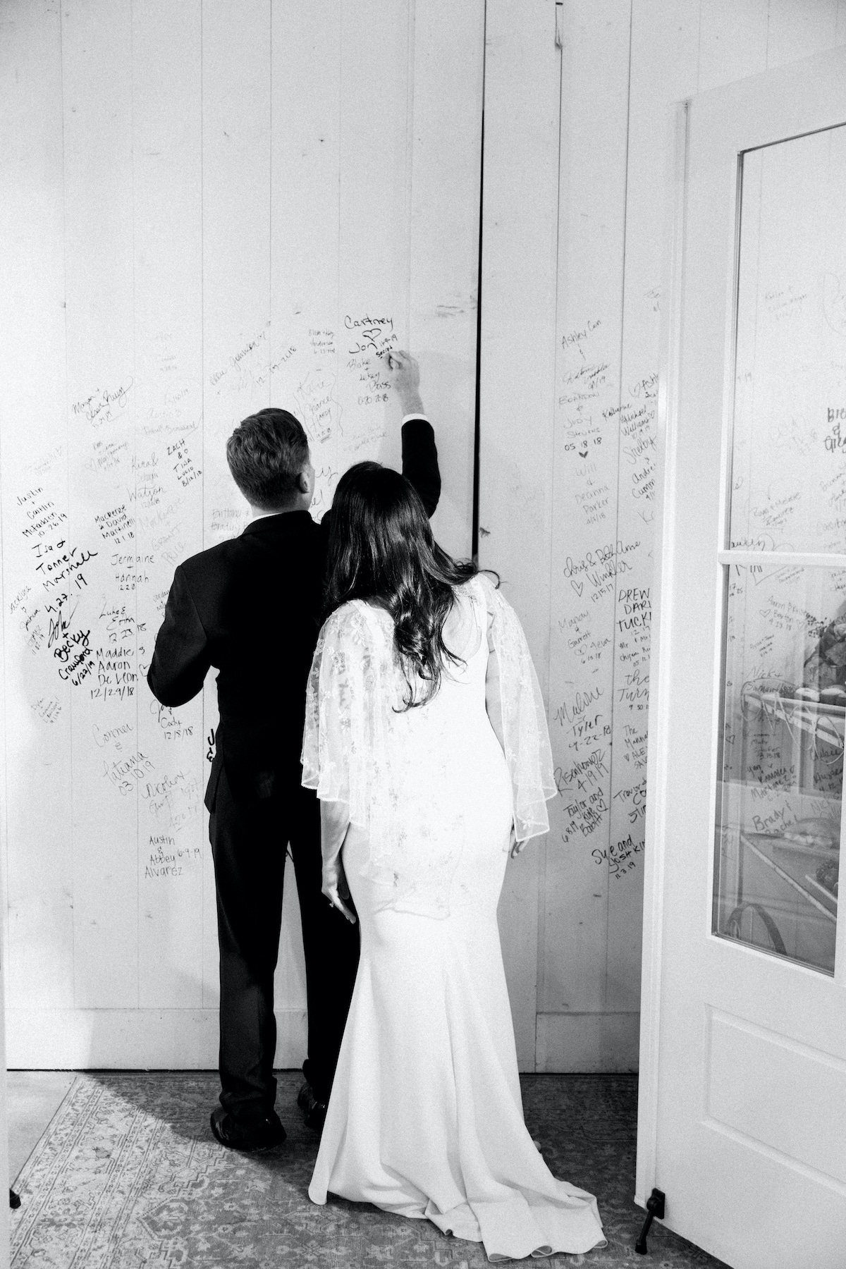 wedding couple signing wall of white barn