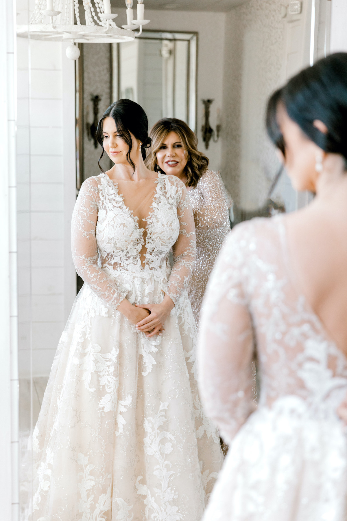 bride getting ready in lace dress with mother