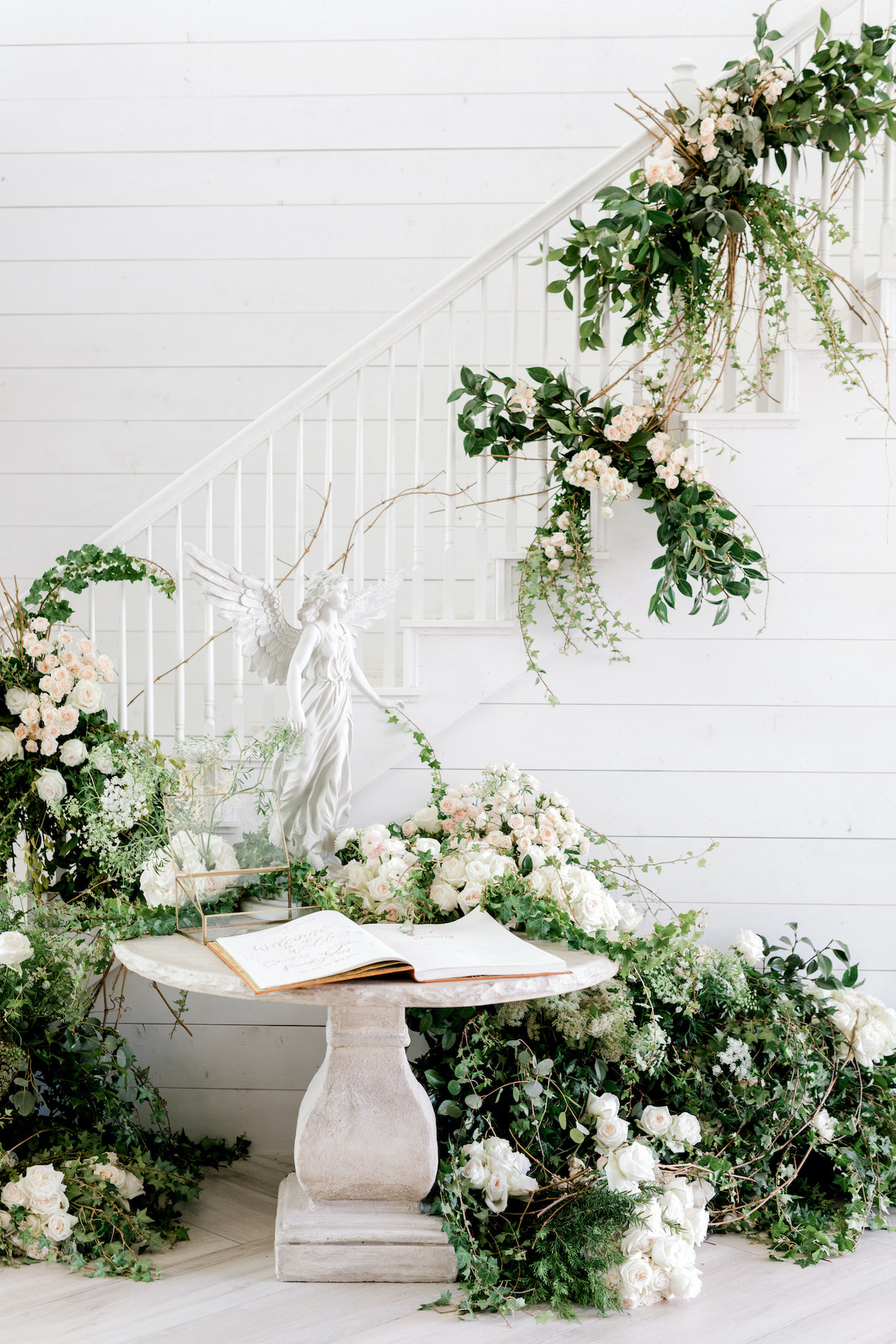 guest book on rustic stone table surrounded by floral garlands