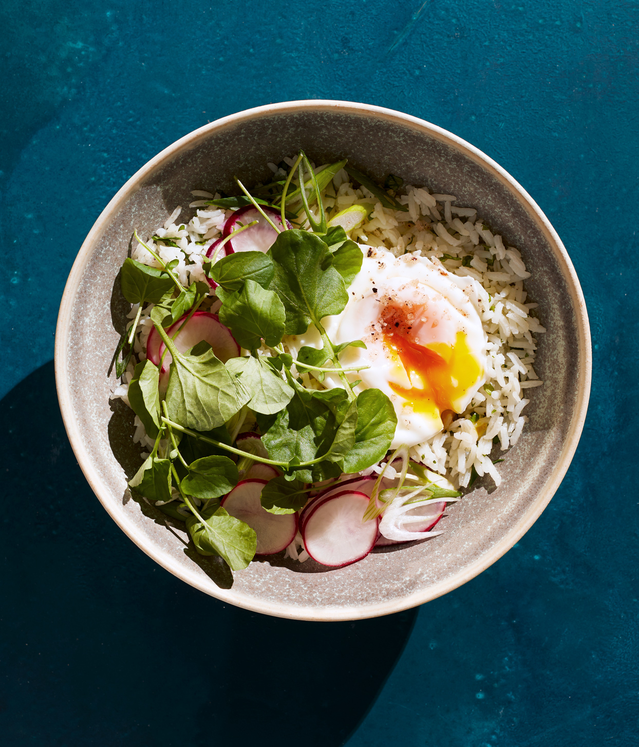 cilantro rice bowl with poached eggs and greens topped with radish slices