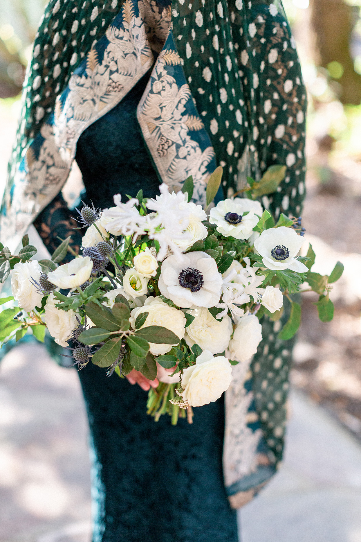 bride in traditional attire holding white and blue wedding bouquet