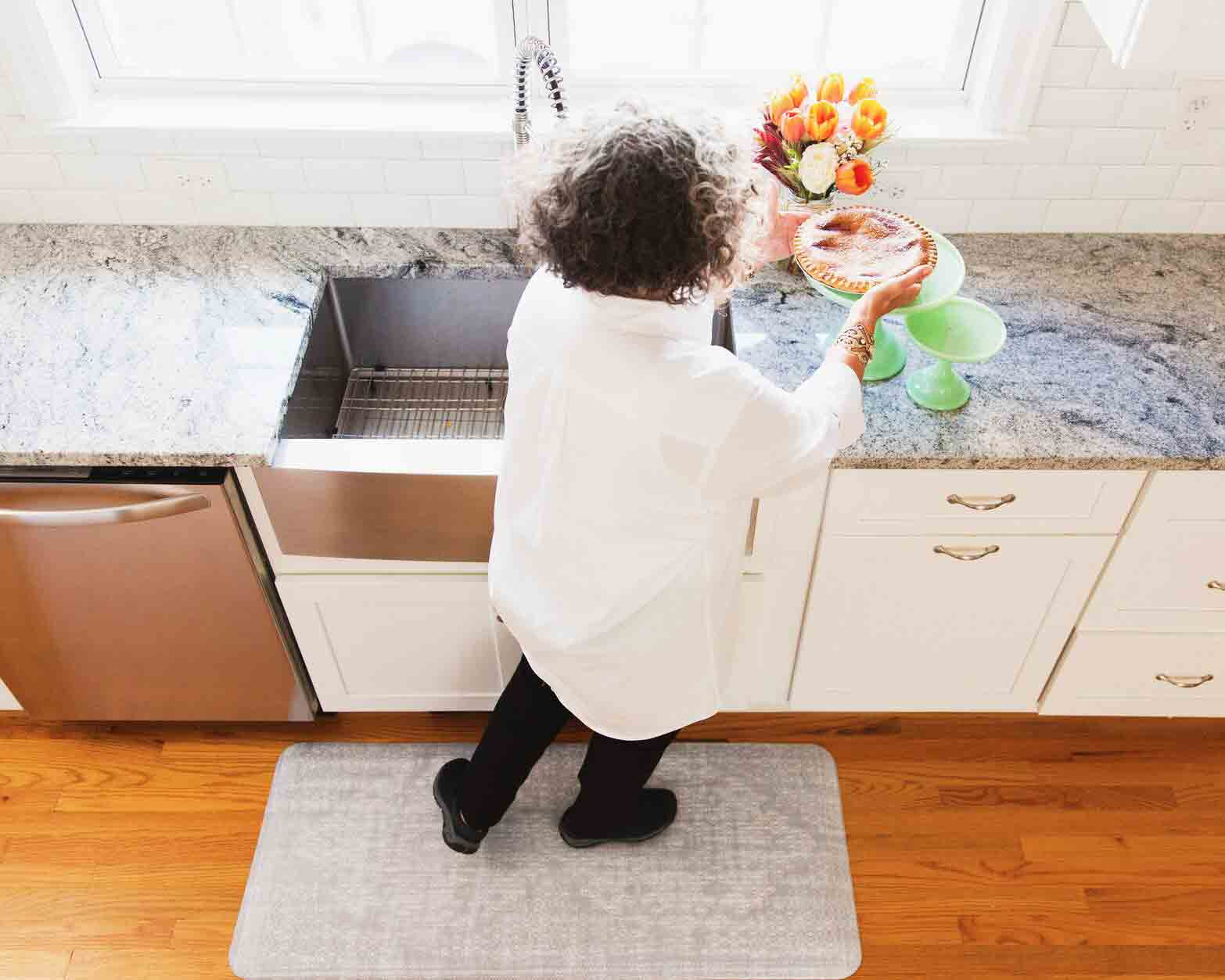 rear view of woman standing on antifatigue mat in kitchen