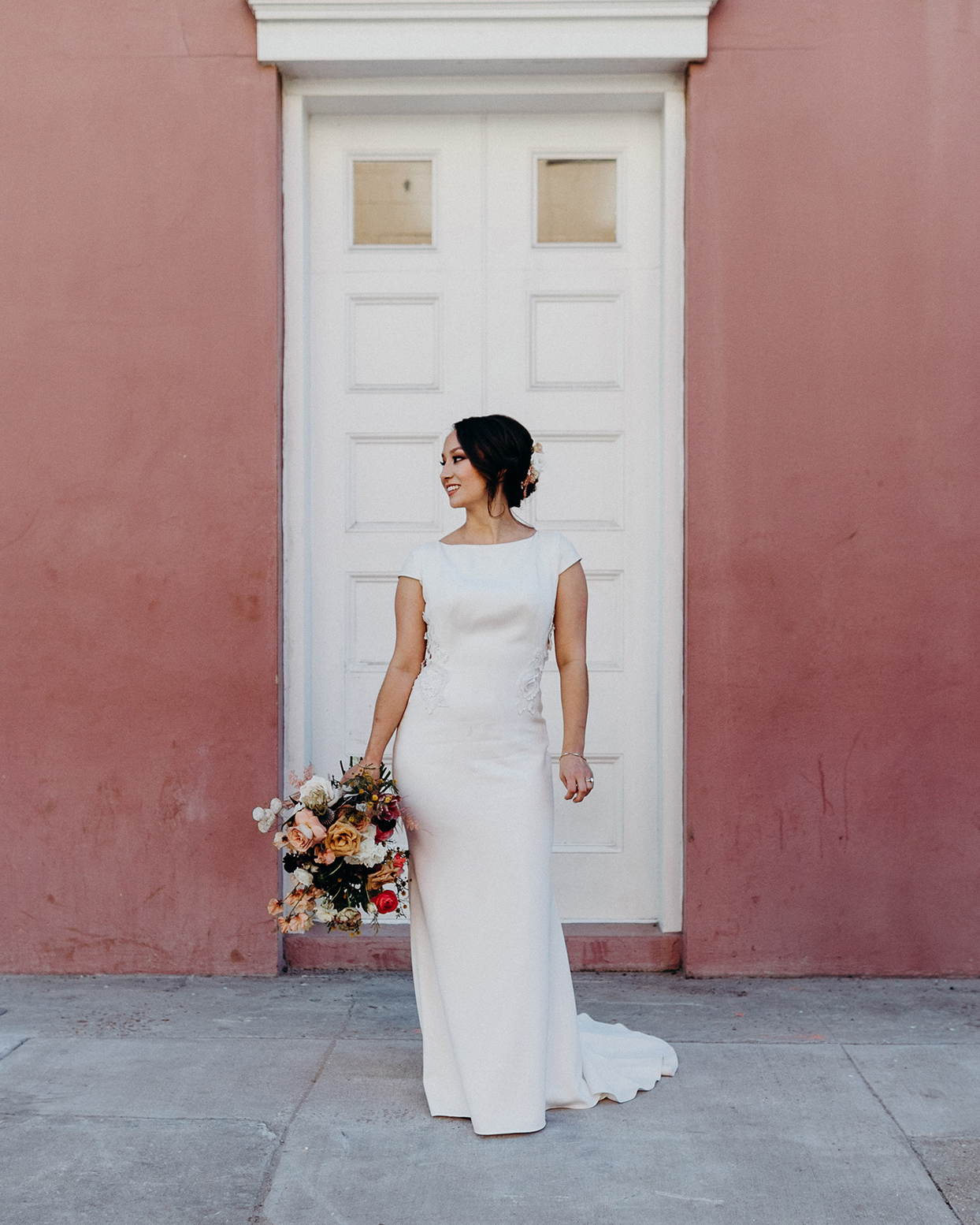 bride in simple white dress in front of muted pink wall
