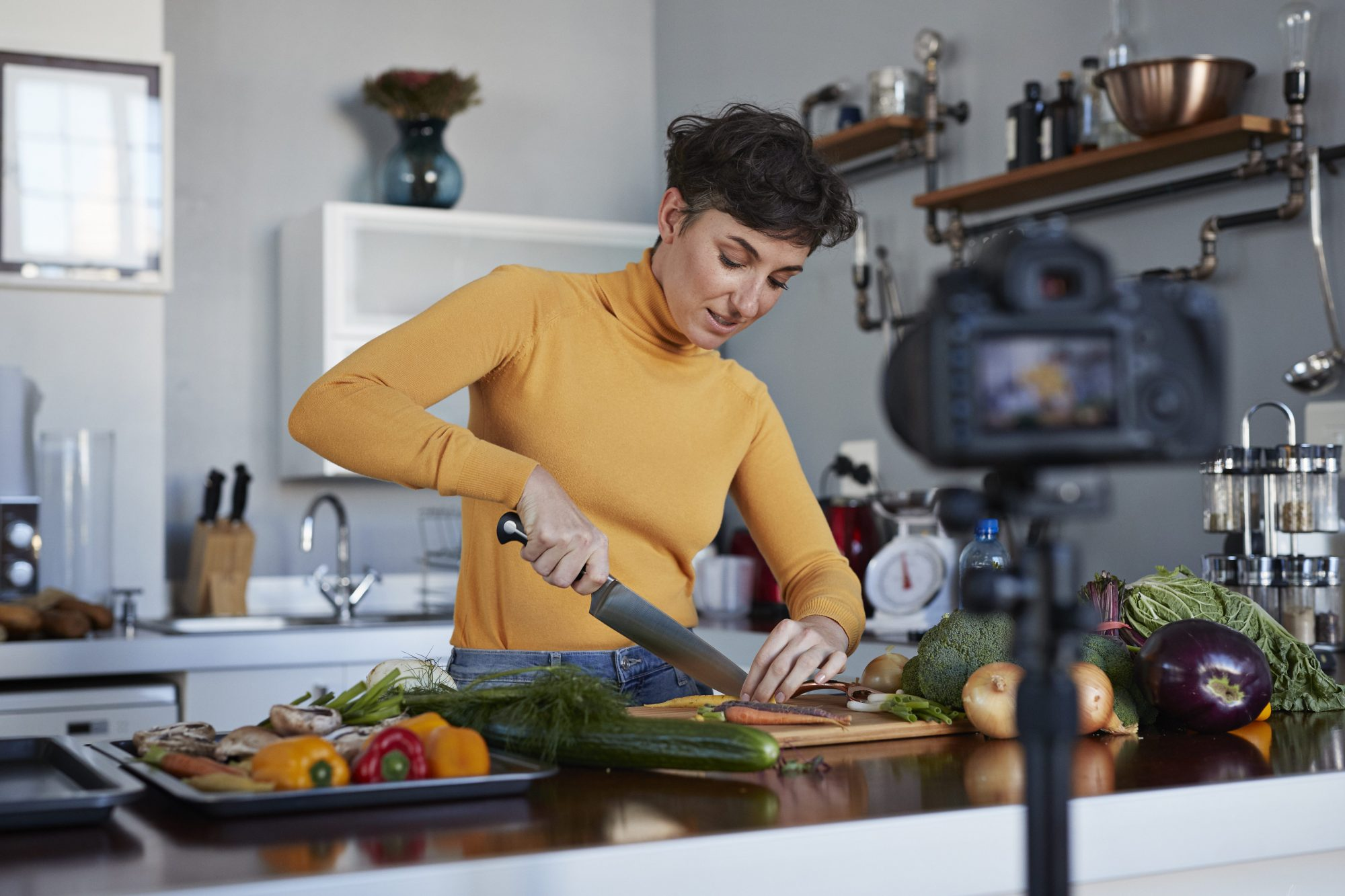 woman cooking meal in front of camera