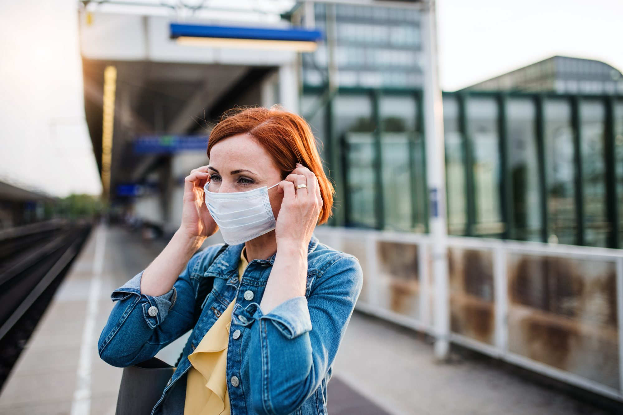 woman wearing fask mask waiting for a train