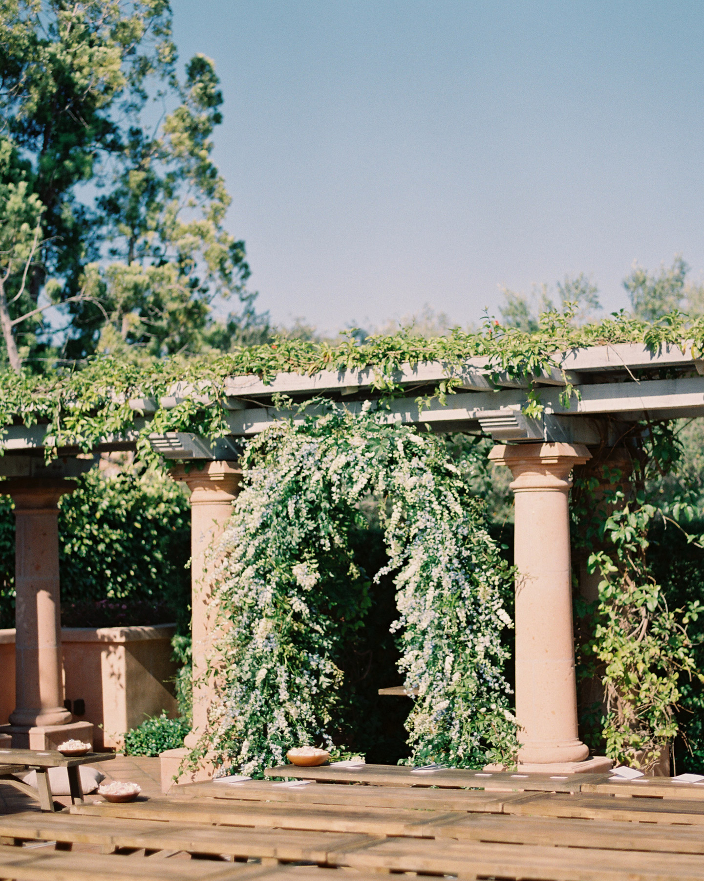 outdoor ceremony space full floral greenery arch