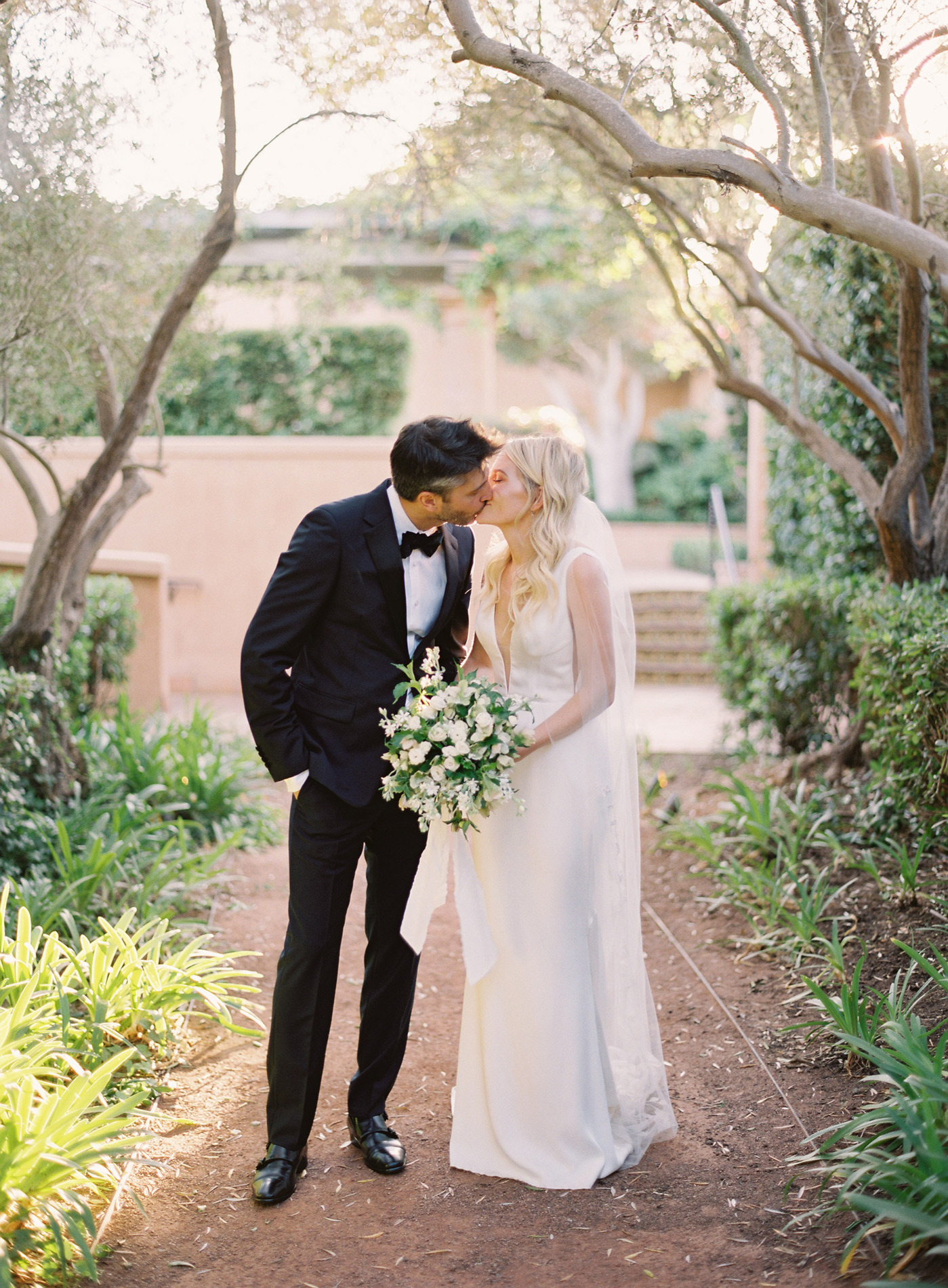 wedding couple kissing on pathway under trees