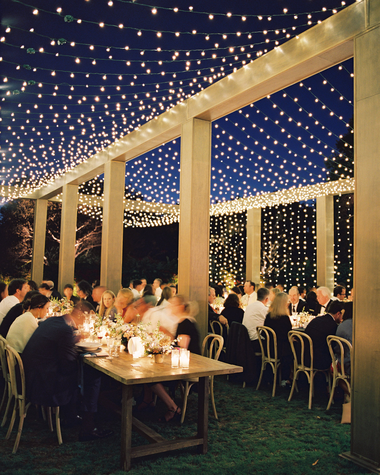 night shot guests at tables gold columns with strings of white lights