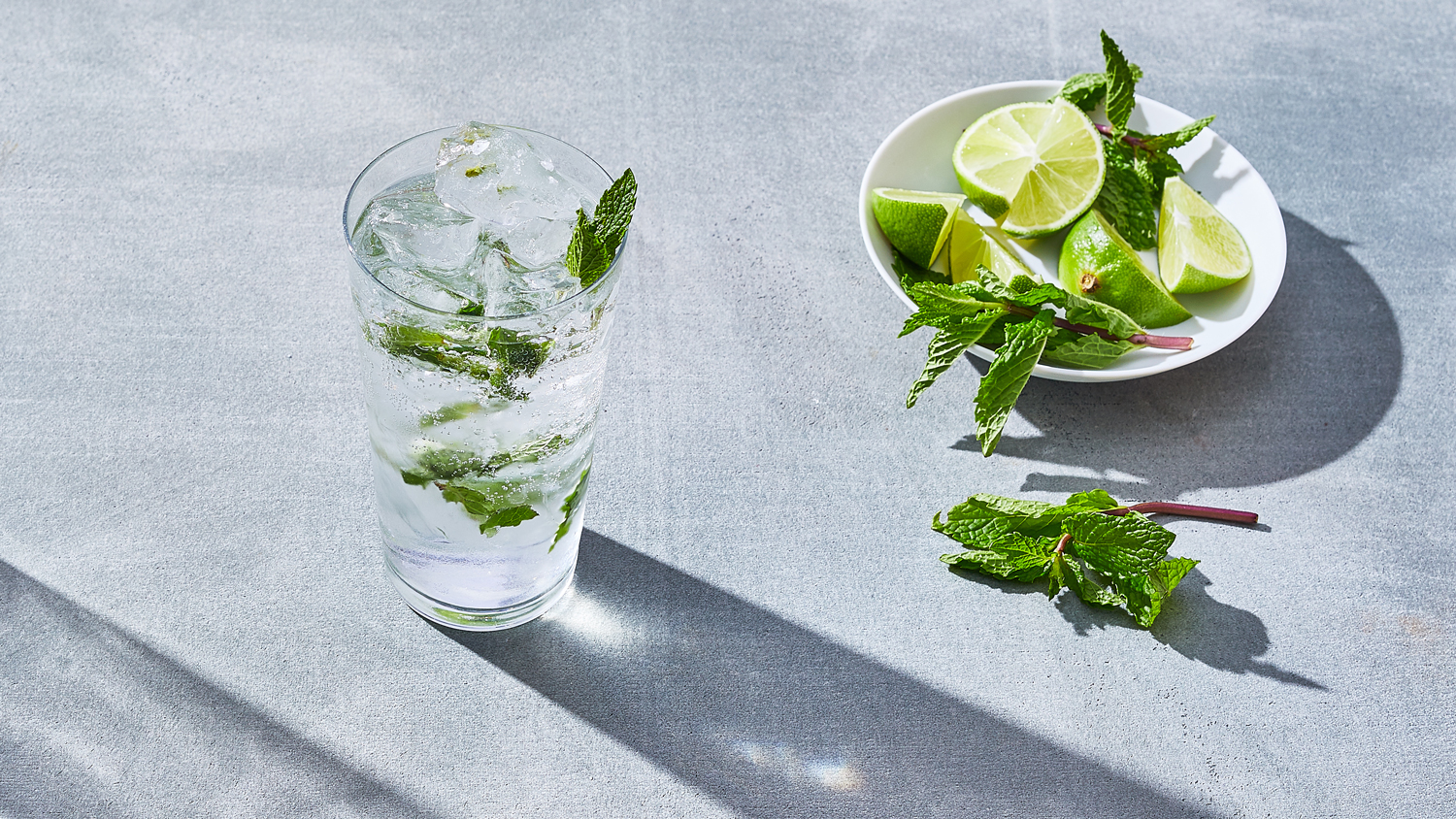 glass of mojito next to plate of limes