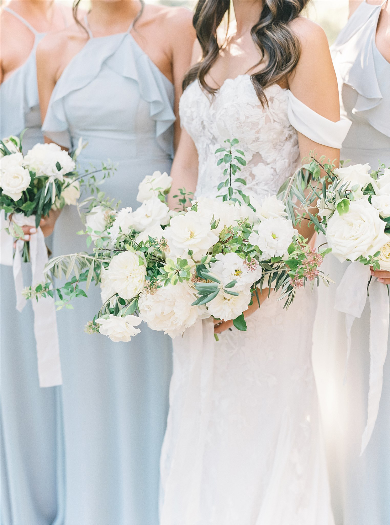 Bride's bouquet with roses, peonies, and olive branches in shades of white, ivory, and green