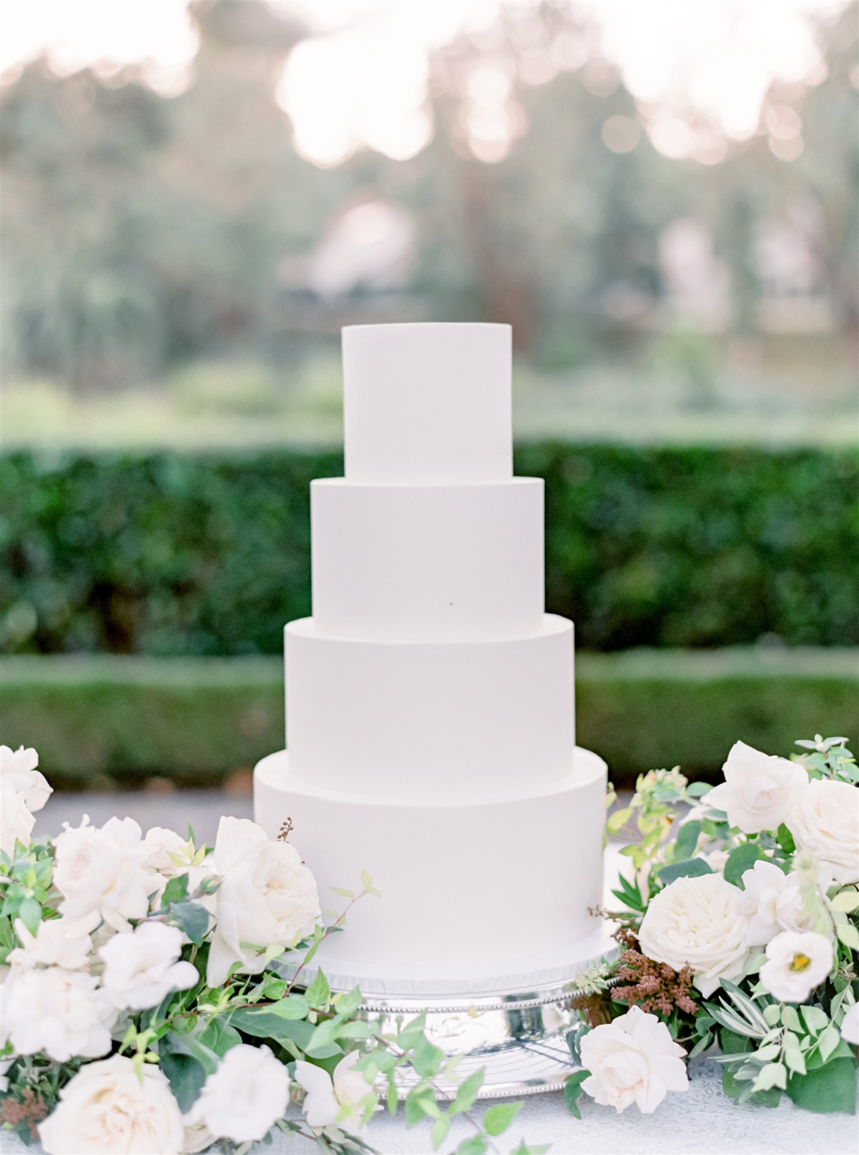 Minimalist white wedding cake on a silver pedestal