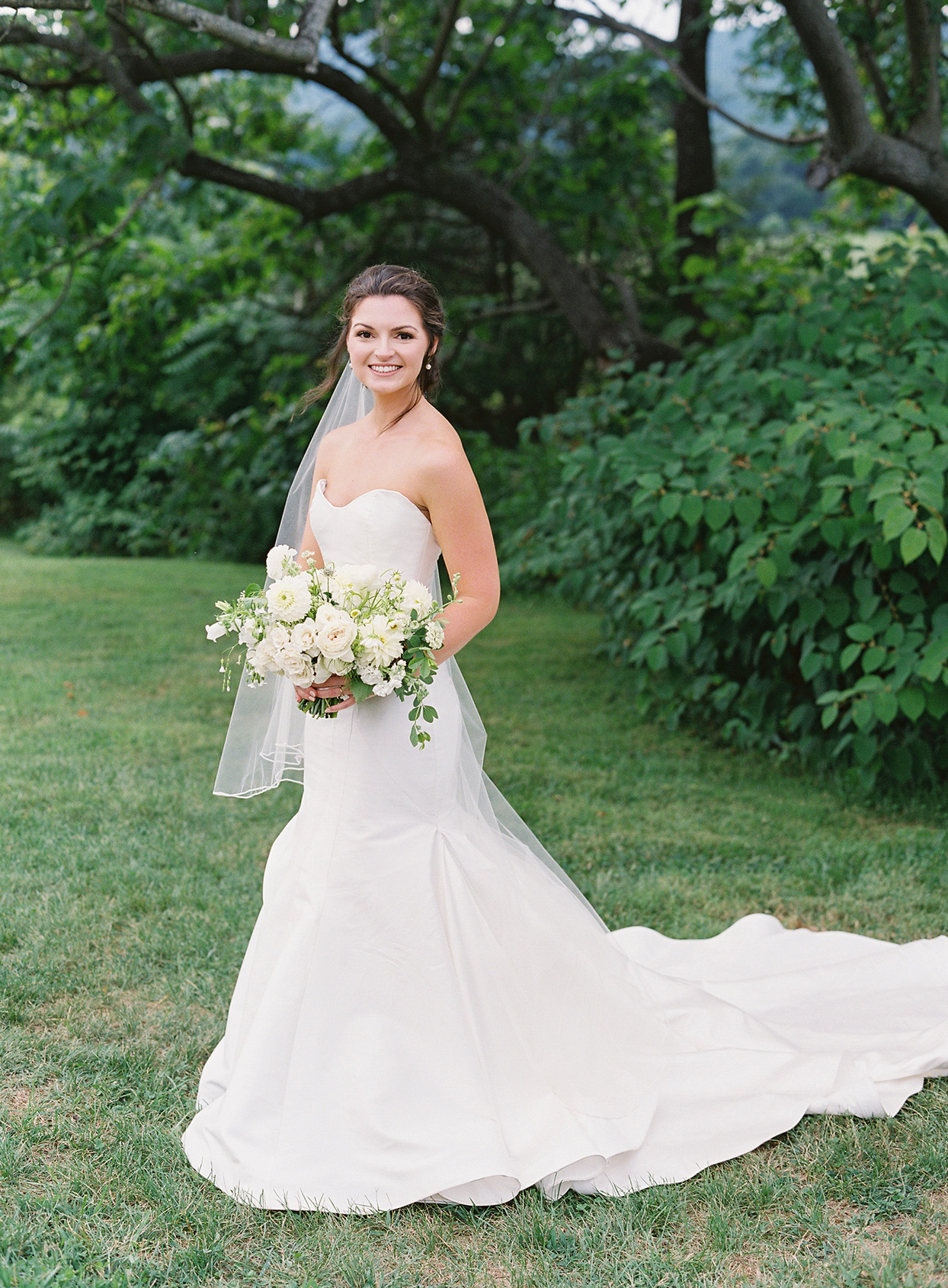bride in white dress on manicured lawn