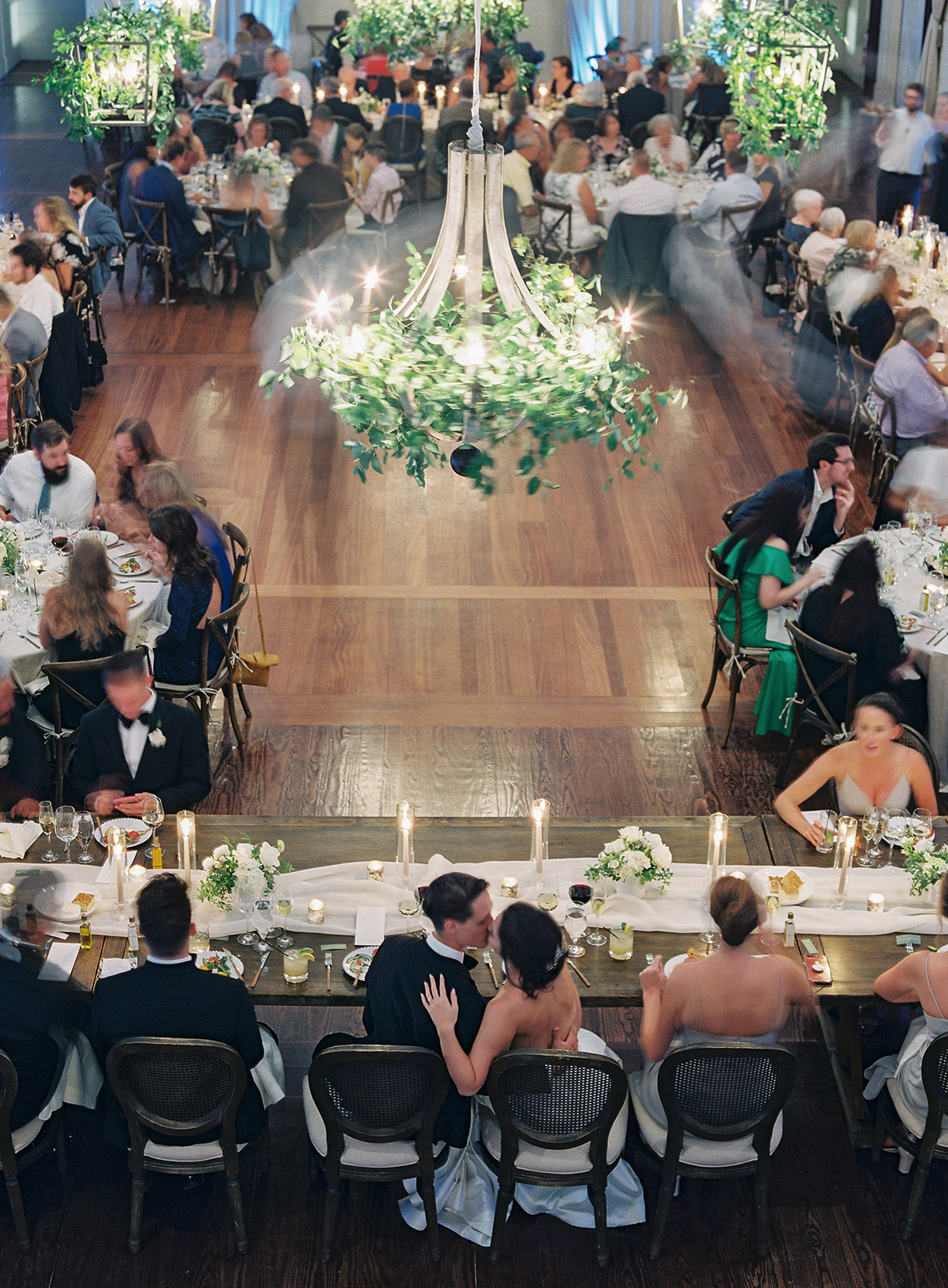 couple kissing at head table during reception dinner under chandelier