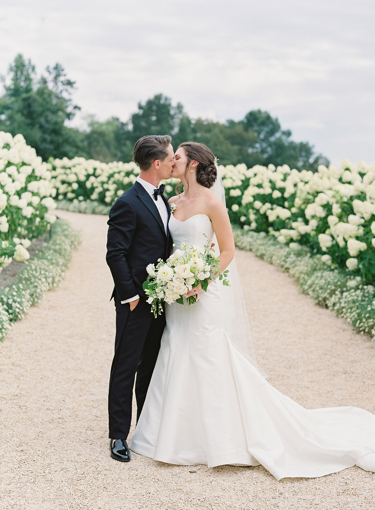 wedding couple kissing on gravel walkway during first look