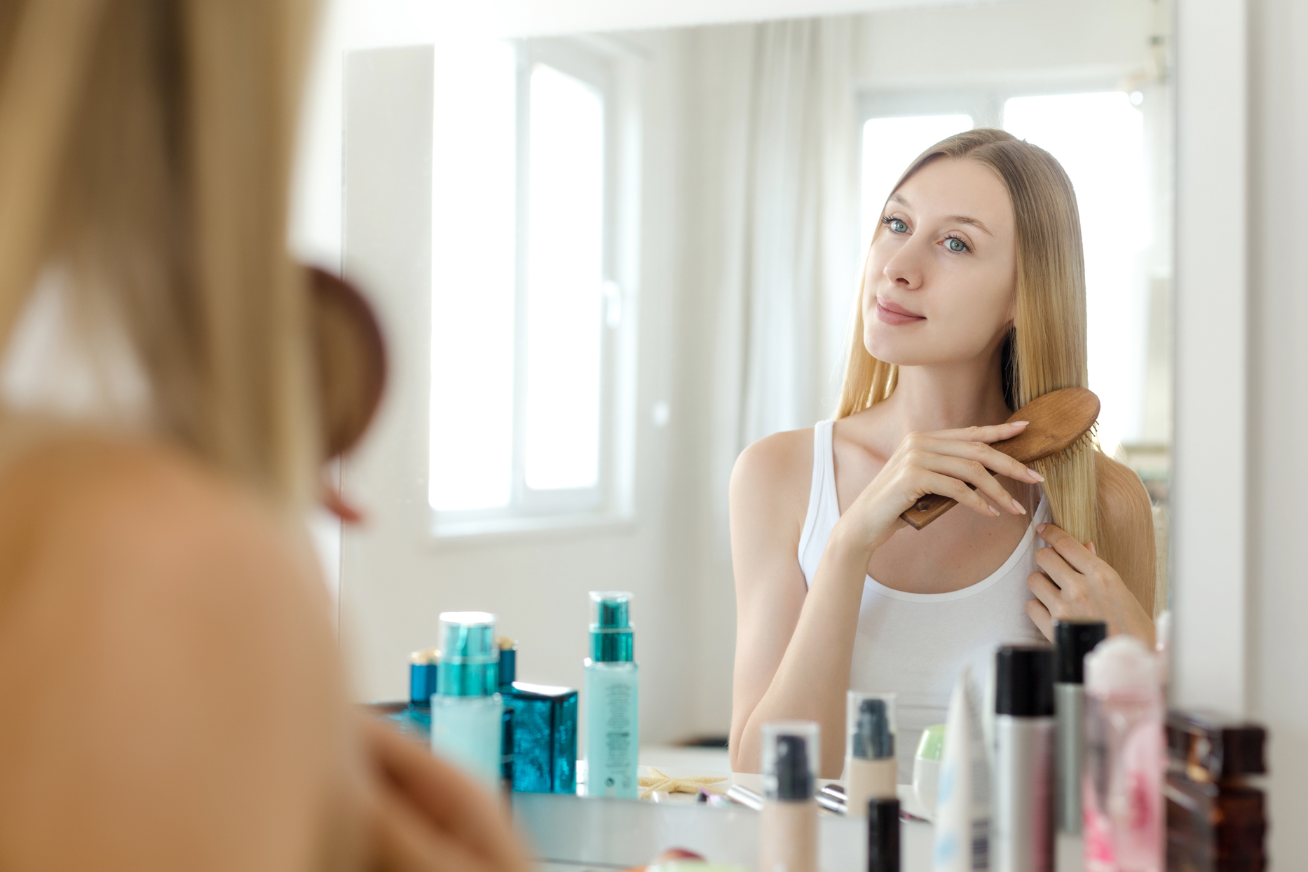 woman looking in mirror brushing hair