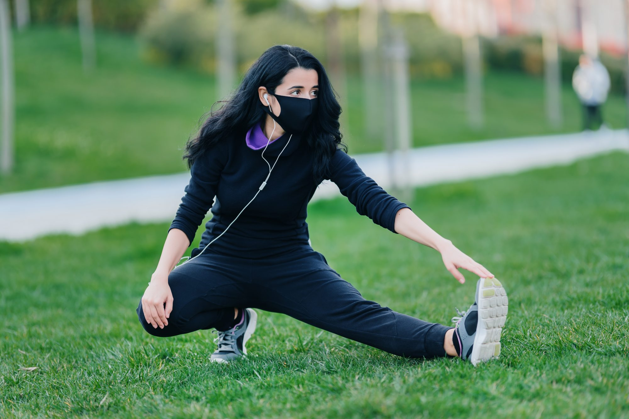 woman stretching with mask on