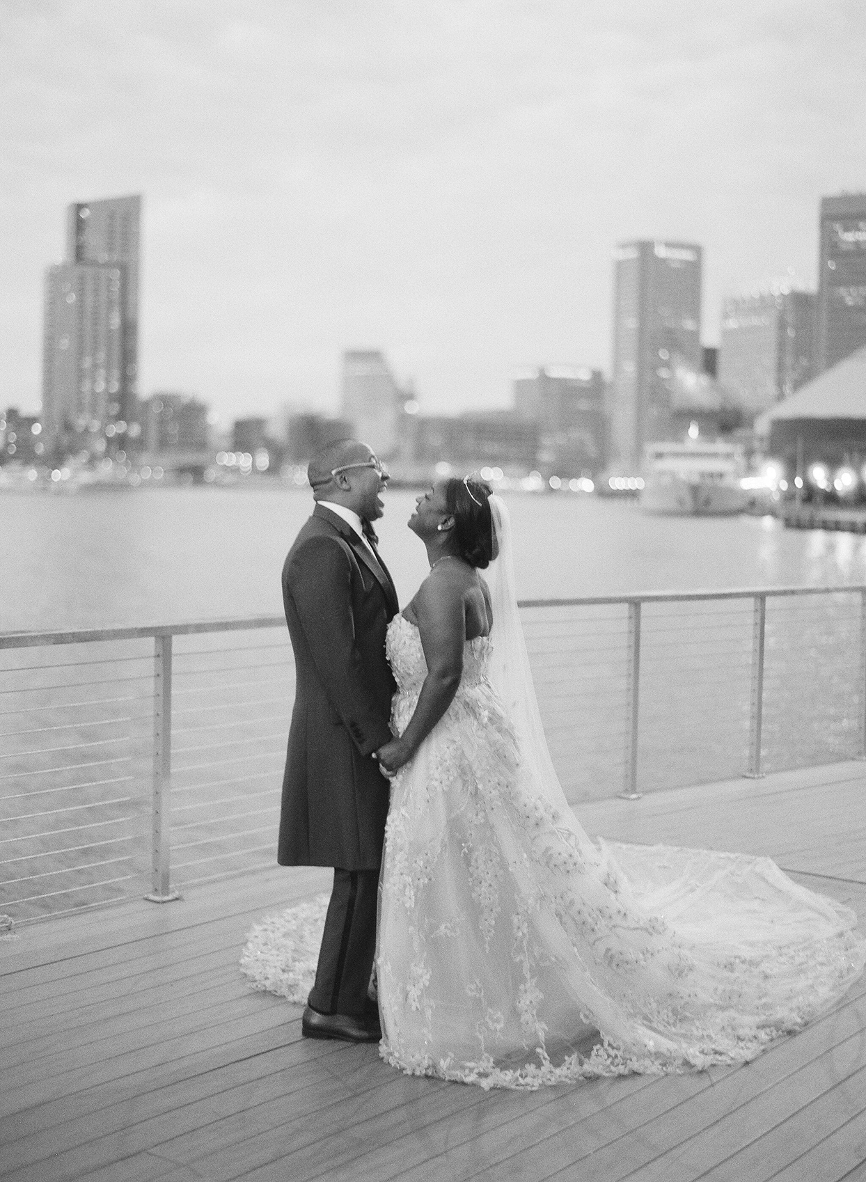wedding couple holding hands and laughing together overlooking river
