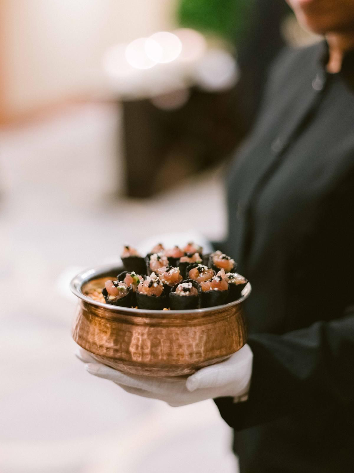 server holding copper dish of wedding appetizers