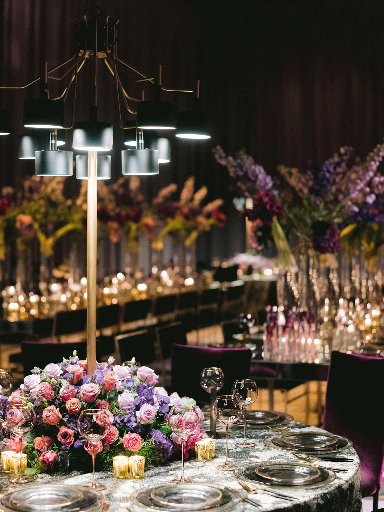 elegant black round tables with pink, purple and gold floral centerpieces