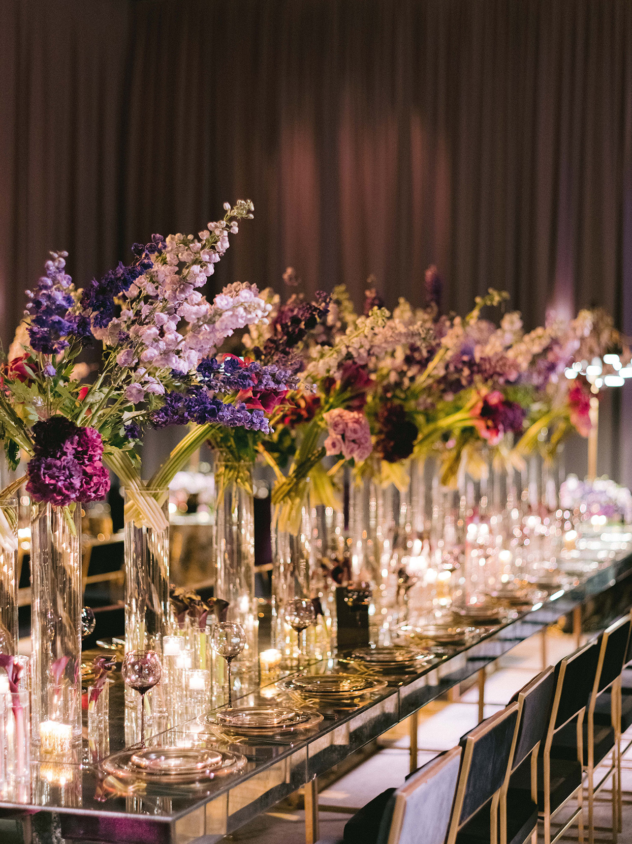 long reflection reception tables with tall vases on flowers and low candles