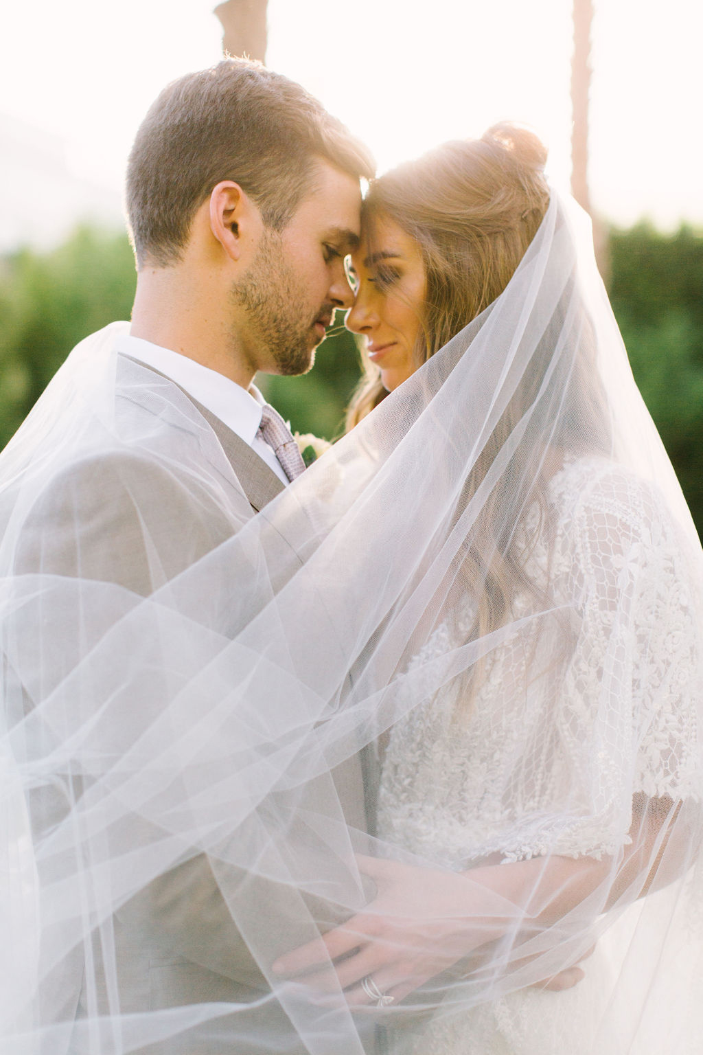 wedding portrait couple embracing with bride's veil flowing around them