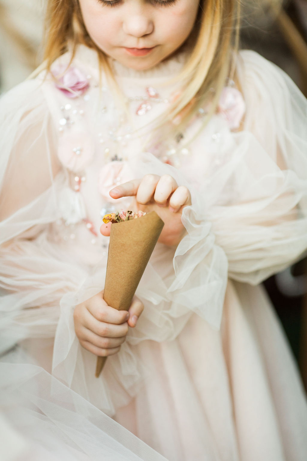 flower girl holding cone of petals
