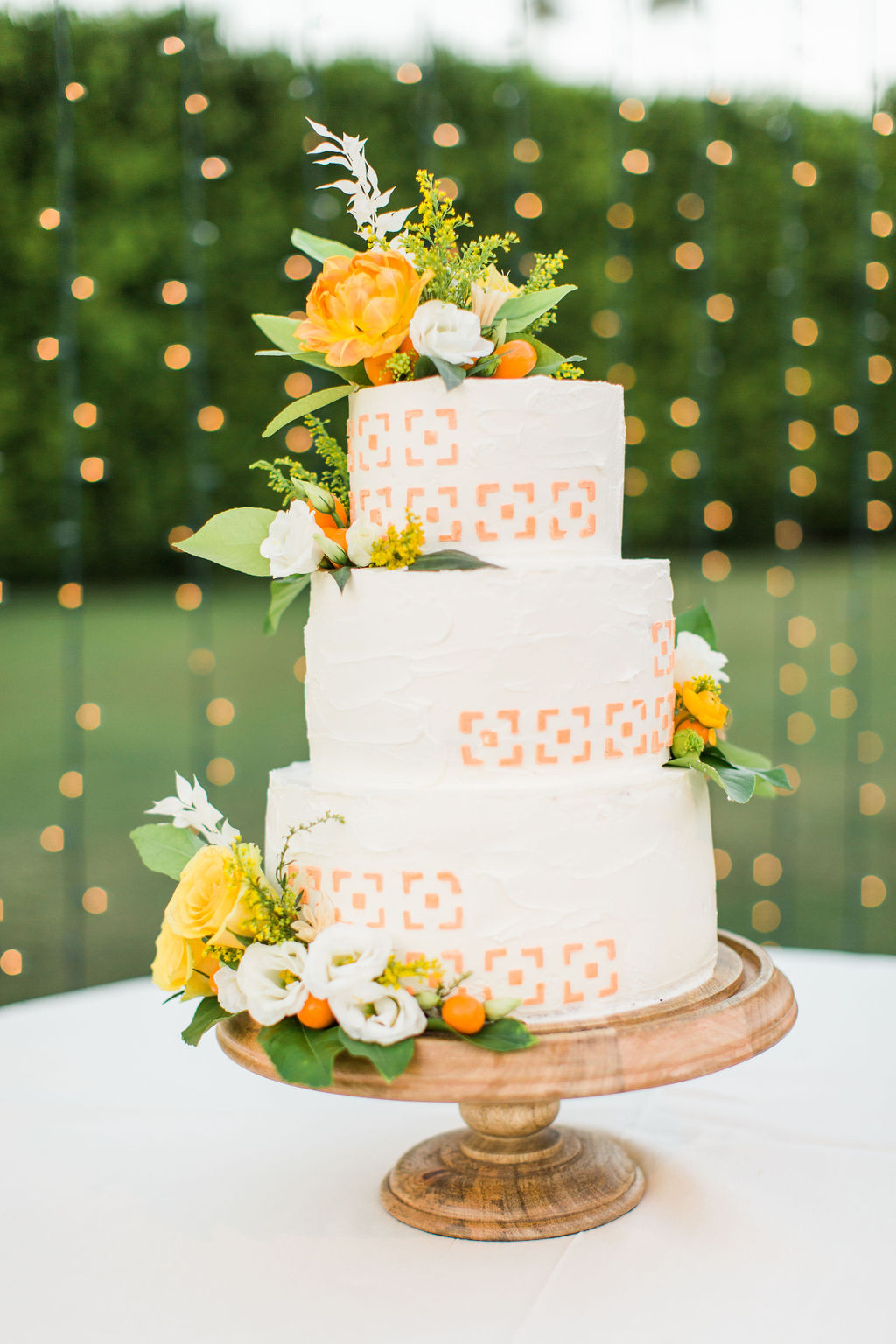 white wedding cake with citrus colored accents and flowers