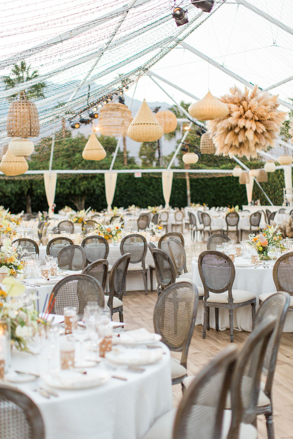 elegant outdoor reception tent with white round tables