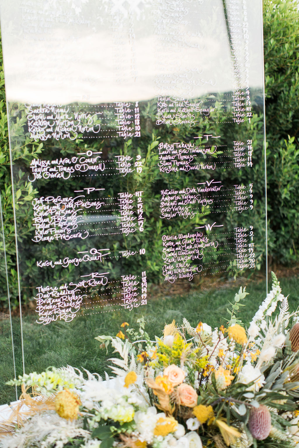 clear wedding seating chart board with flowers at the base