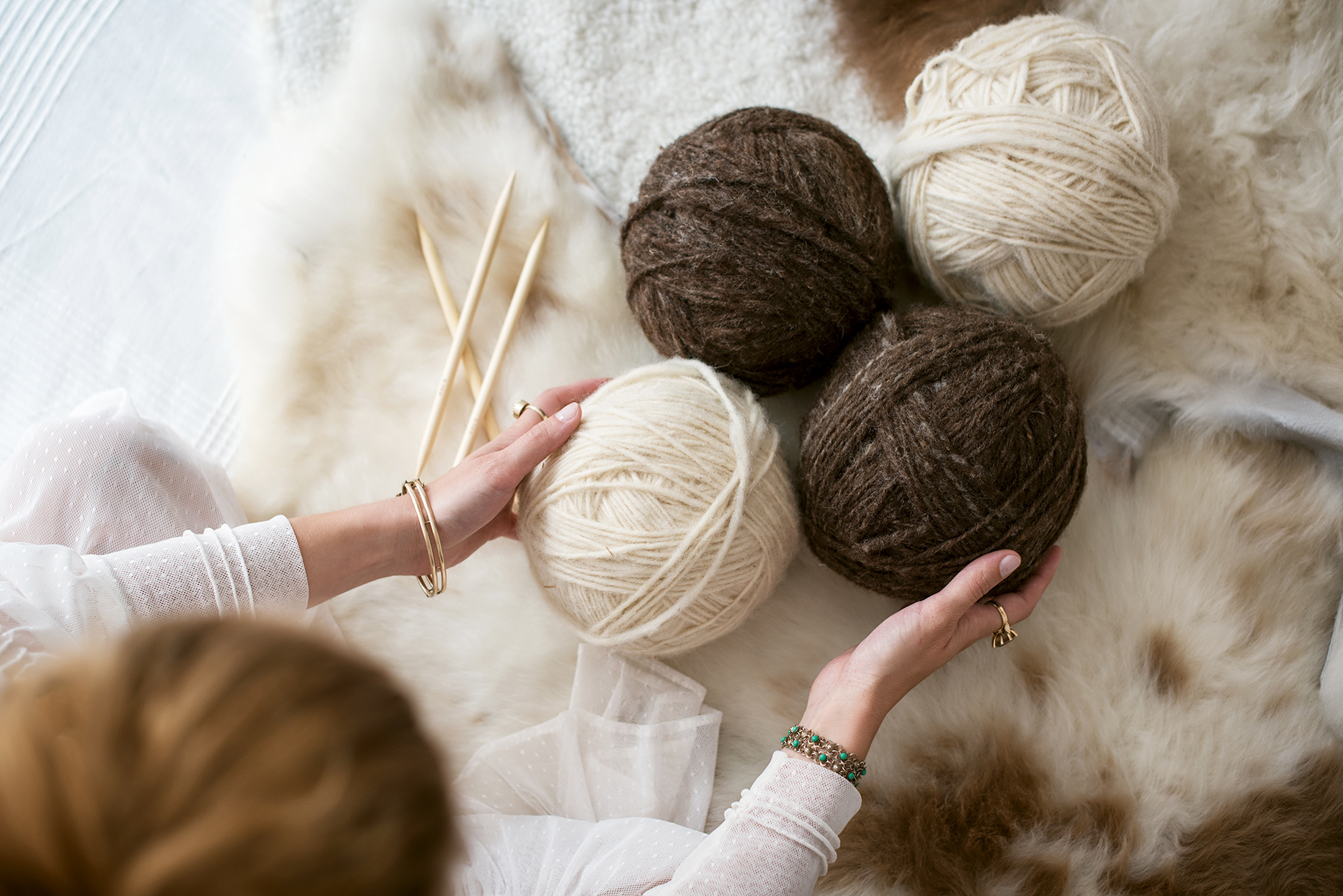 Woman holding onto balls of yarn