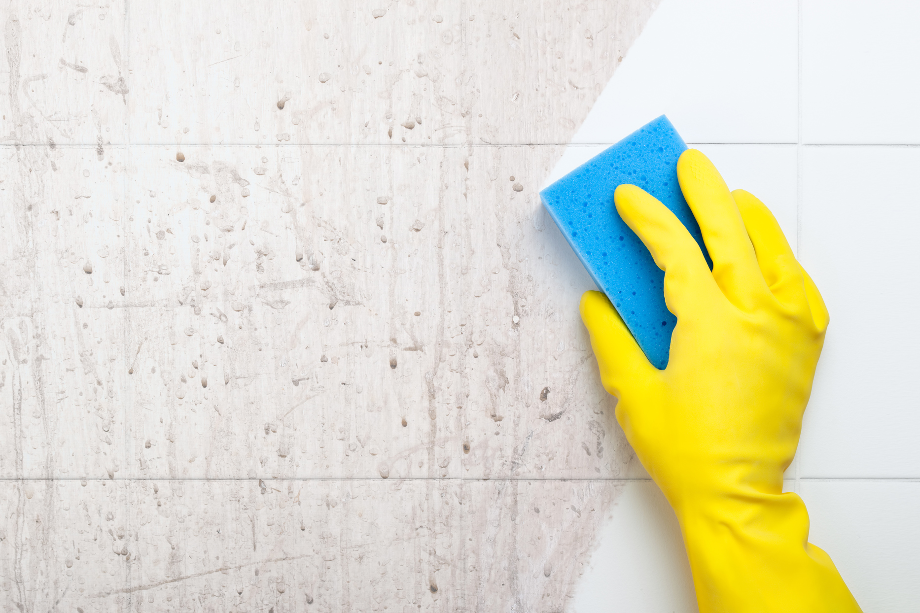 yellow gloved hand cleaning tile with blue sponge