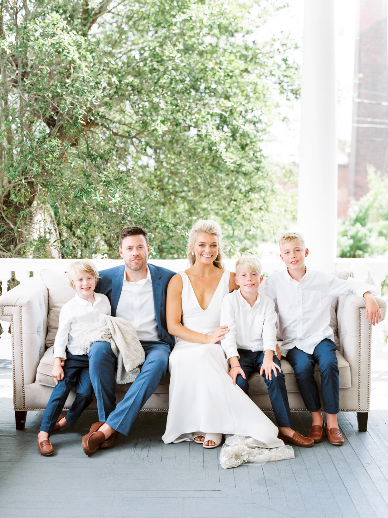 bride and groom with three sons sitting on outdoor couch