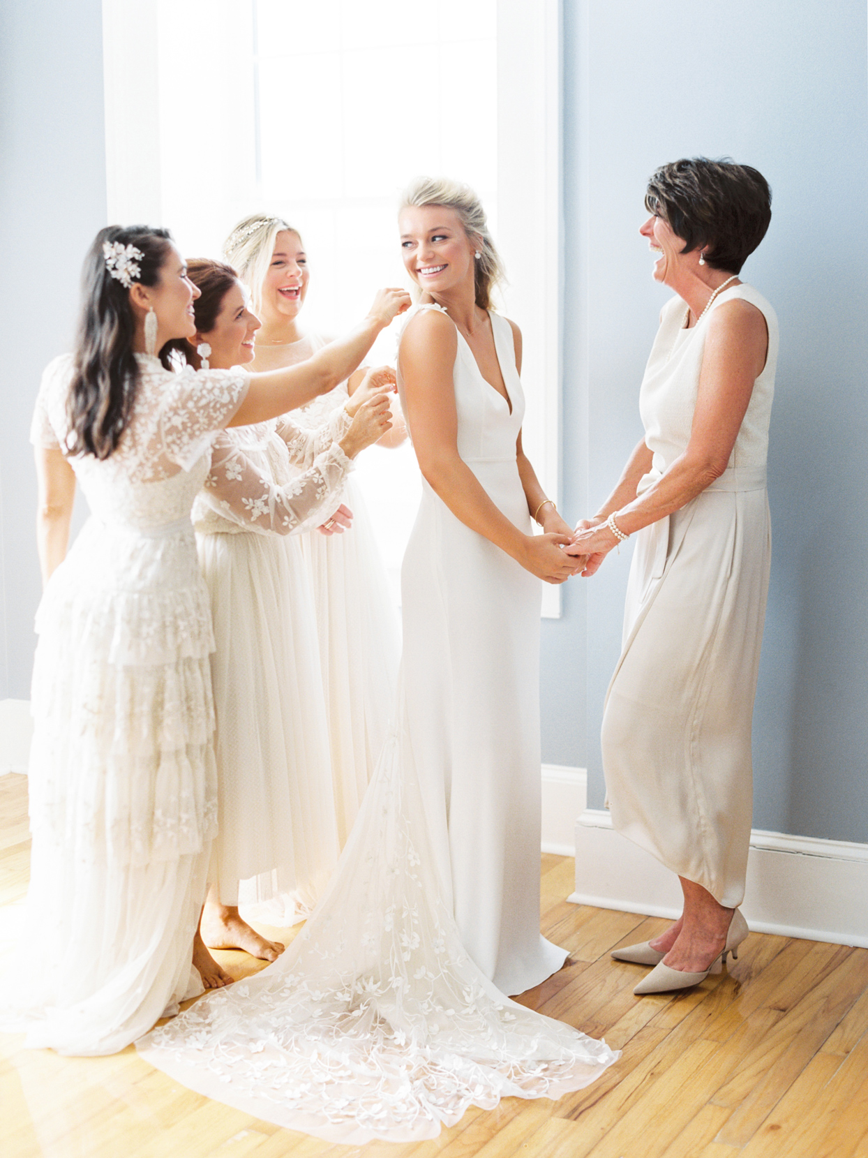 bride with bridesmaids and mother getting ready