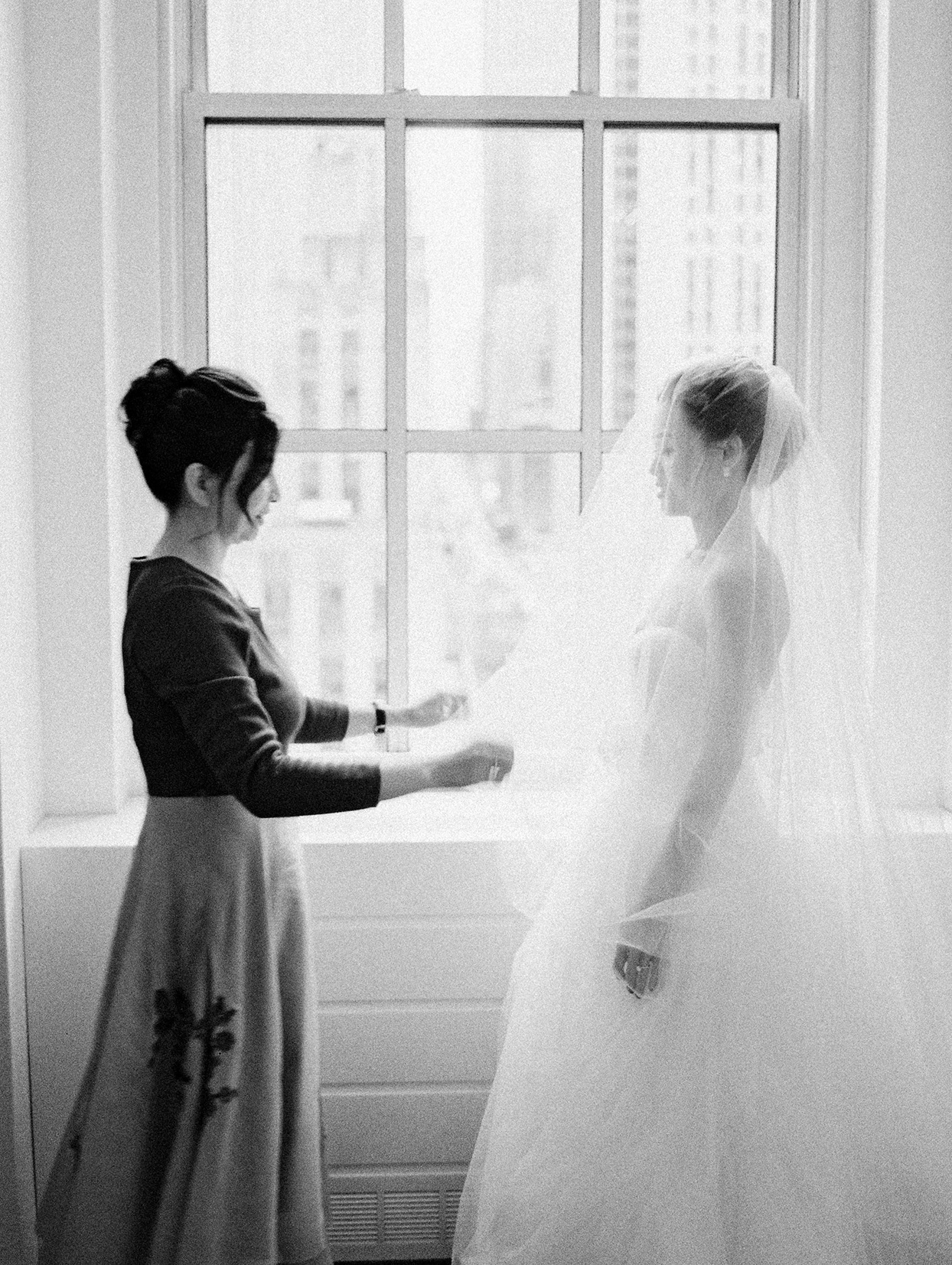 mother helping bride put on her veil in front of window