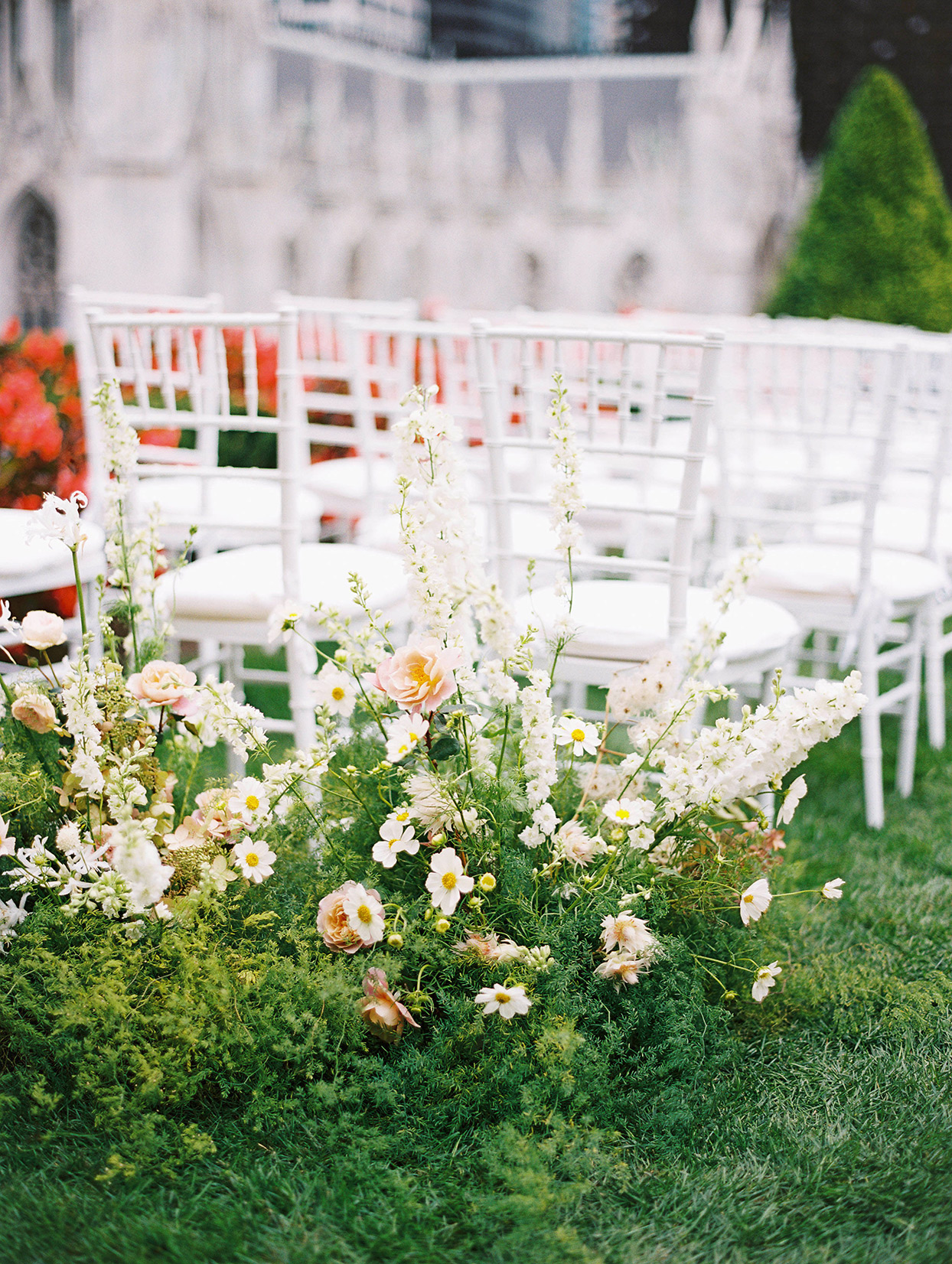 wedding ceremony white chairs with floral decorations