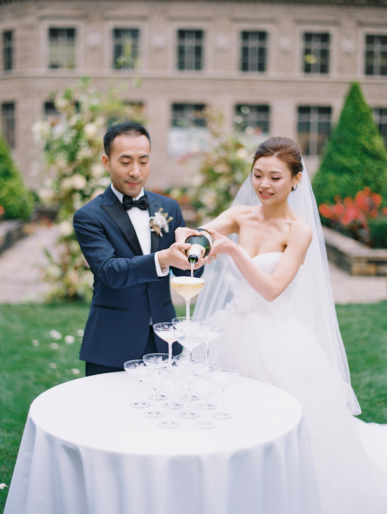wedding couple pouring champagne in glass tower