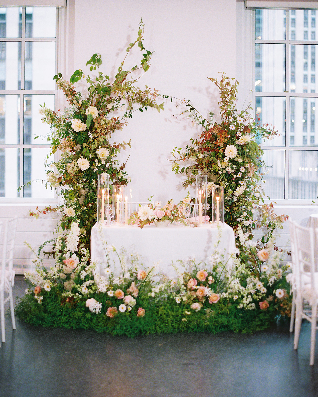 sweetheart table with floral arch and decor at reception