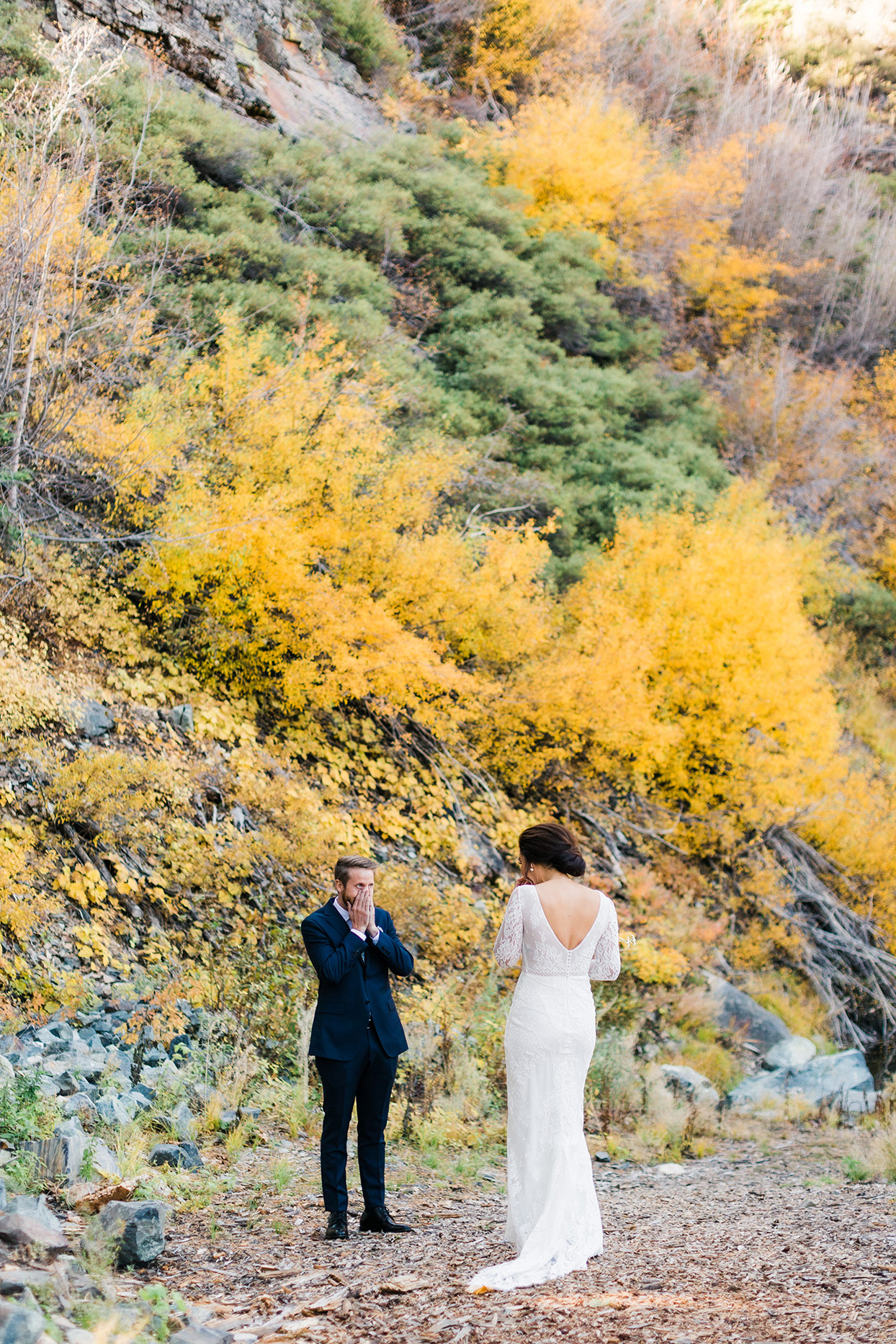 groom covering has mouth during first look in fall foliage