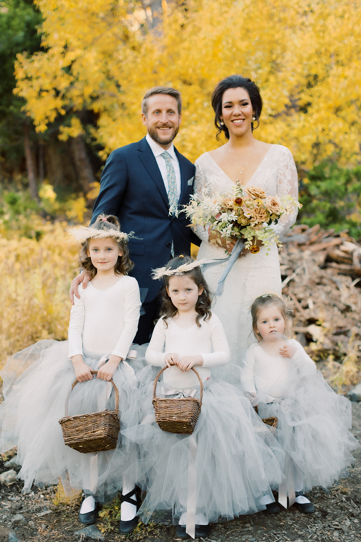 bride and groom posing with three flower girls in gray tulle skirts holding wicker baskets