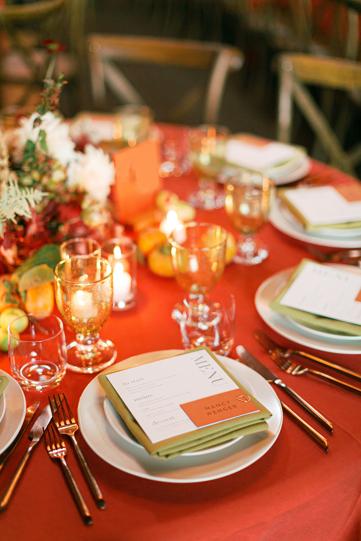 elegant reception table with orange table cloth, flowers, and candles